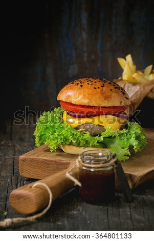 Fresh homemade burger with black sesame seeds on wooden cutting board with fried potatoes, served with ketchup sauce in glass jar over old wooden table with dark background. Dark rustic style. - stock photo