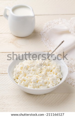 Fresh homemade cottage cheese and jug of cream on a white wooden table - stock photo