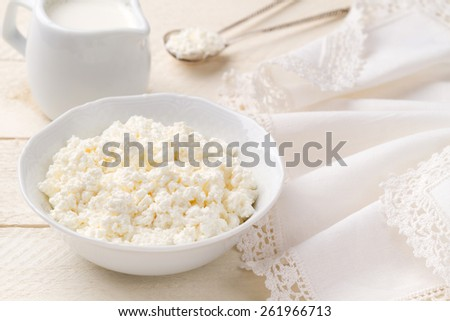 Fresh homemade cottage cheese and jug of cream on a white wooden table (closeup) - stock photo