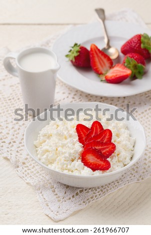 Fresh homemade cottage cheese with strawberries and cream jug - stock photo