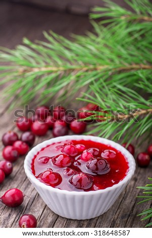 Fresh homemade cranberry sauce in portion bowl on dark wooden background with a scattering of ripe cranberries. selective Focus - stock photo