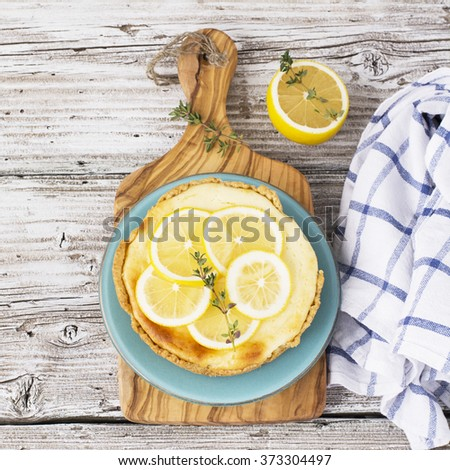 Fresh homemade cream cheese sweet cake for breakfast with slices of lemon and thyme on olive board on a simple light wooden background. selective Focus - stock photo