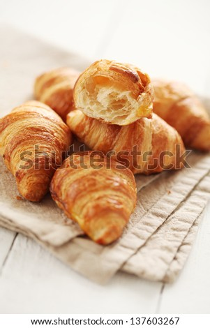 Fresh homemade french croissants on a linen tablecloth - stock photo