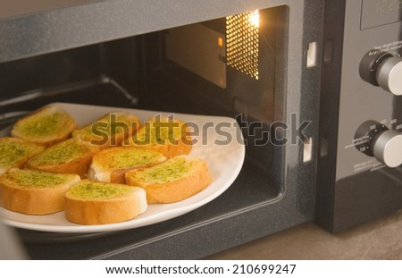 Fresh homemade garlic bread in microwave oven - stock photo