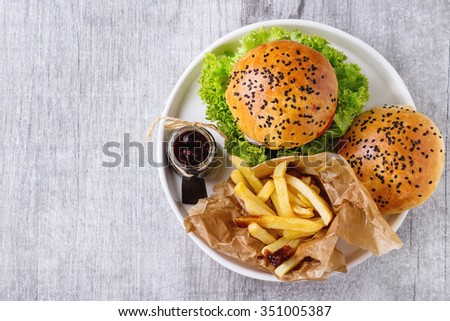 Fresh homemade hamburger with black sesame seeds in white plate with fried potatoes, served with ketchup sauce in glass jar over gray wooden surface. Top view - stock photo