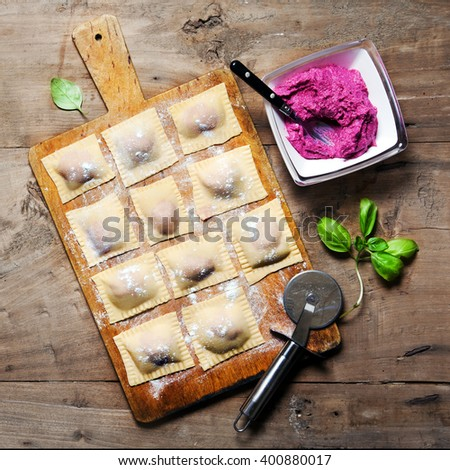fresh homemade Italian ravioli with beetroot and ricotta cheese on a wooden table - stock photo