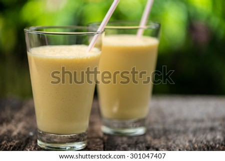 Fresh homemade mango  smoothie in a glass, served outside in a garden on a wood table - stock photo