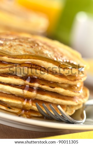 Fresh homemade pancakes with maple syrup (Selective Focus, Focus on the syrup drop running down) - stock photo