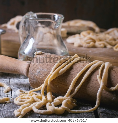Fresh homemade pici pasta on wood chopping board over old wooden table with flour, aluminum pan, rolling-pin and galss jug of water. Dark rustic style. Square image with selective focus - stock photo