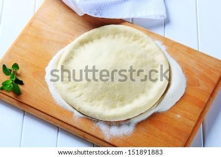 Fresh homemade pizza dough on floured wooden board - stock photo