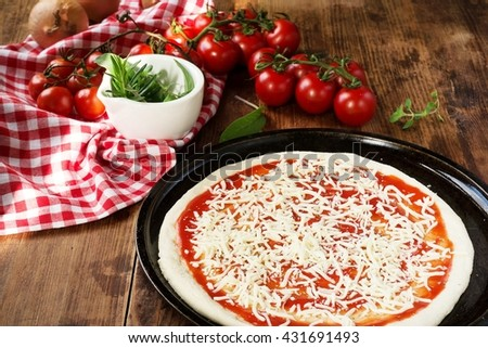 fresh homemade pizza dough with tomato sauce and cheese - stock photo