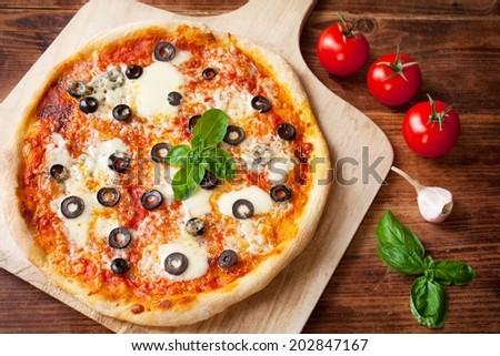 Fresh Homemade Pizza Margherita with Olives, Mozzarella and Basil  - stock photo