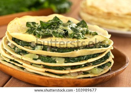 Fresh homemade savory crepes layered with chard (mangold) and onion with cheese on top served on wooden plate (Selective Focus, Focus on the front of the topping) - stock photo