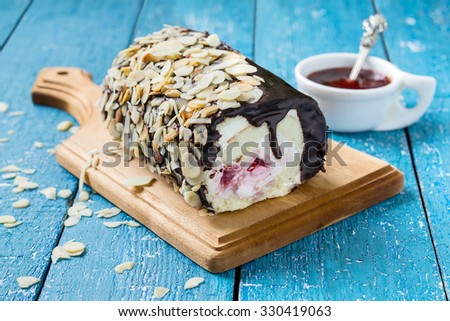 Fresh homemade sponge roll with cream cheese and cherry jam. Decorated with chocolate icing and almond petals. Selective focus - stock photo