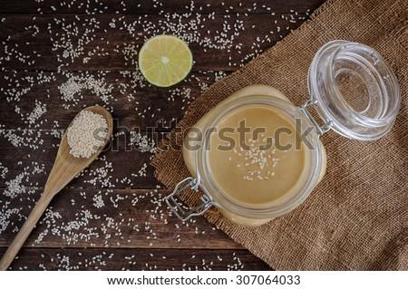 Fresh homemade Tahini (sesame paste) in a glass jar - stock photo