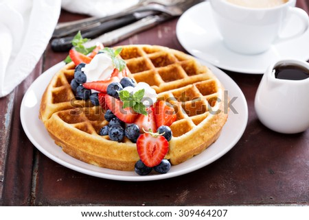 Fresh homemade waffles with ricotta served with whipped cream and berries - stock photo