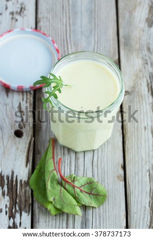 Fresh homemade yogurt salad dressing - delicious and tasty. On wooden table. Natural light, selective focus. - stock photo