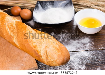 Fresh ingredients for baking crusty French baguette with wheat, eggs and flour and a freshly baked loaf in the foreground - stock photo