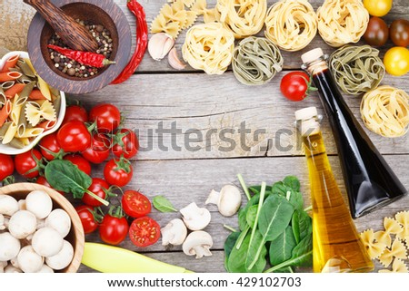 Fresh ingredients for cooking: pasta, tomato and spices over wooden table background with copy space - stock photo