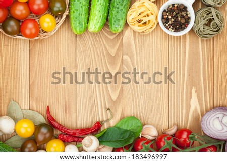 Fresh ingredients for cooking: pasta, tomato, cucumber, mushroom and spices over wooden table background with copy space - stock photo