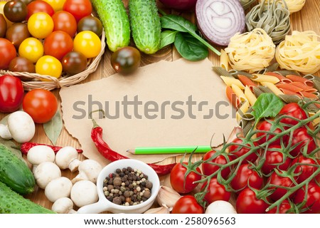 Fresh ingredients for cooking: pasta, tomato, cucumber, mushroom and spices over wooden table background and paper with copy space - stock photo