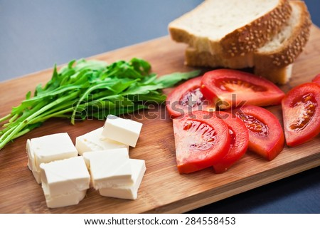 Fresh ingredients for cooking: tomato, salad rocket, bread, feta cheese - stock photo