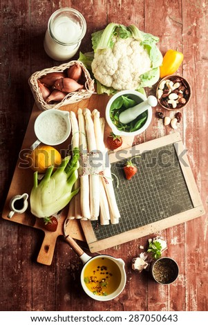 Fresh ingredients for delicious vegetarian cuisine with cauliflower, asparagus, kohlrabi, fresh herbs and spices around a blank school slate on a rustic wooden counter, overhead view - stock photo