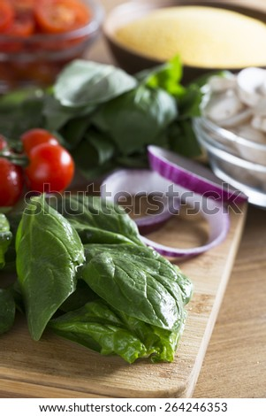 Fresh ingredients for making polenta dish.  Spinach in the foreground with red onion slices, cherry tomatoes, mushrooms and polenta in the background  out of focus.  Vertical image. - stock photo