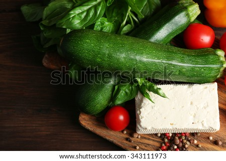 Fresh ingredients for preparing zucchini rolls on wooden background  - stock photo