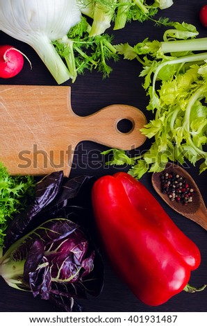 Fresh ingredients for salad: vegetables and spices over wooden table background and cutting board with copy space. Healthy eating. Healthy food. Food flat lay. Top view.  - stock photo