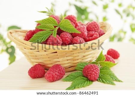 fresh is juicy raspberries in the woven basket - stock photo