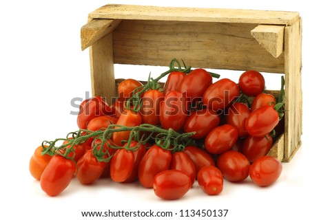fresh italian cherry tomatoes on the vine in a wooden crate on a white background - stock photo