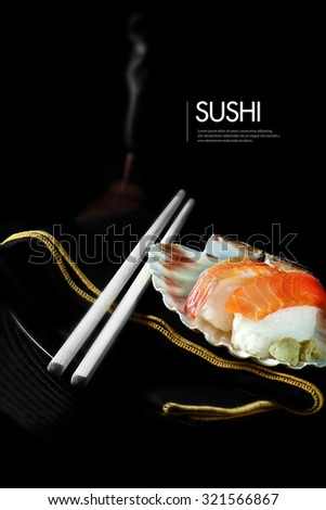 Fresh Japanese sushi with chop sticks, burning incense and luxury napkin against a black background. Generous accommodation for copy space. - stock photo