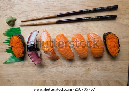 Fresh japanese sushi with chopsticks and wasabi on wood cut board - stock photo