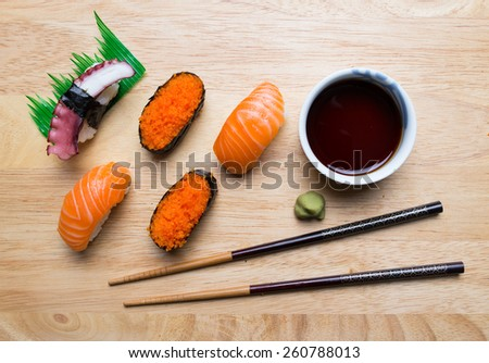 Fresh japanese sushi with wasabi, soy suace and chopsticks on wood background - stock photo