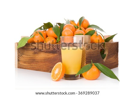 Fresh juice and ripe mandarines with green leaves in wooden crate. Organic fresh mandarines, healthy fruit eating.  - stock photo
