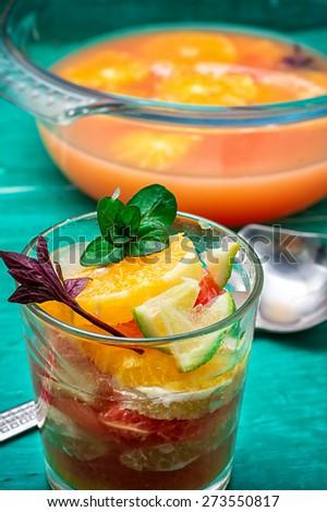 fresh juice from oranges,kiwi and grapefruit on turquoise wooden background.Selective focus - stock photo