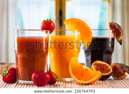 Fresh juice, mix fruits orange, strawberry, lime, apple and ficus drinks with window background.  - stock photo