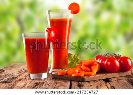 fresh juice, mix vegetable, carrot and tomato drinks with nature green background  - stock photo