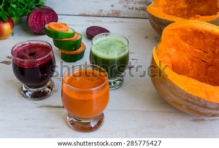 Fresh juice of carrots, pumpkins, cucumbers and beets in jars. Vegetables on the table - stock photo
