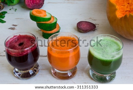 Fresh juice of cucumber, pumpkin, carrots, beets on the table. Fresh orange juice in a glass. Vegetable fresh juice in a glass - stock photo