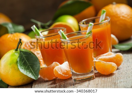 Fresh juice of ripe mandarins in a small glass with striped straw, selective focus - stock photo
