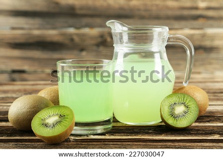 Fresh juice with kiwi on brown wooden background - stock photo