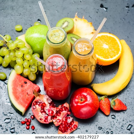 Fresh Juices Smoothie Three Bottles made Red Green Orange Fruits Water Melon Strawberry Apple Kiwi Grapes Orange Mango Pomegranate Tropical Selective focus Square - stock photo