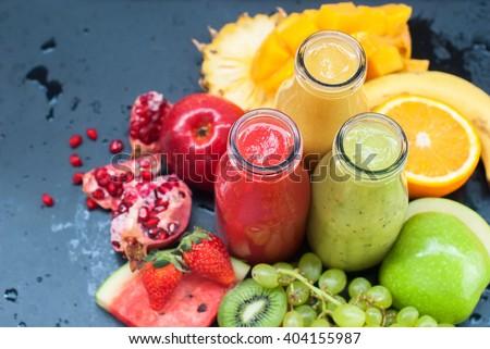 Fresh Juices Smoothie Three Bottles Red Green Orange Tropical Fruits Water Melon Strawberry Apple Kiwi Grapes Orange Mango Banana Pine Apple Pomegranate Grape Selective focus - stock photo