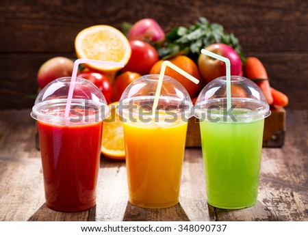Fresh juices with fruits and vegetables on wooden background - stock photo
