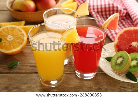 Fresh juices with fruits on wooden table - stock photo