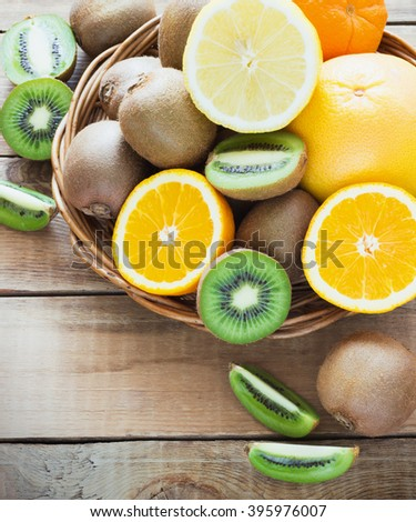 Fresh juicy citrus fruits in a basket on a wooden background kiwi, orange, lemon, grapefruit - stock photo