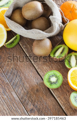 Fresh Juicy Kiwi, orange, lemon, grapefruit  fruit in bag on brown wooden background - stock photo