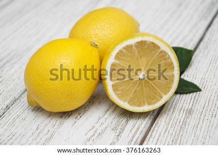 Fresh juicy lemon with leaves on a wooden background - stock photo